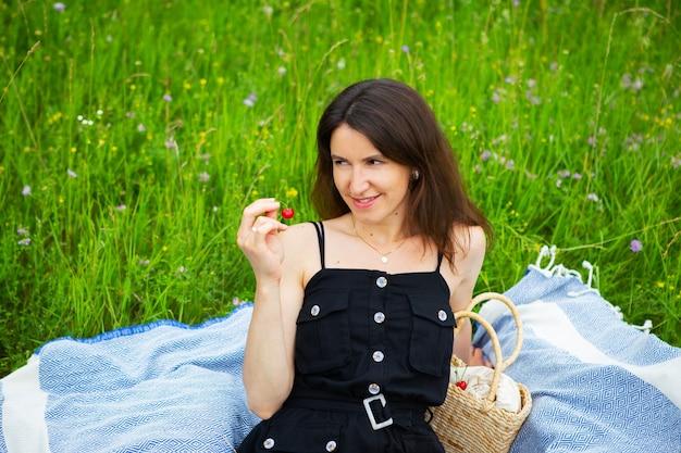 Dziewczyna trzyma czerwoną wiśnię siedząc na niebieskiej kratę. rekreacja na świeżym powietrzu, zbliżenie.