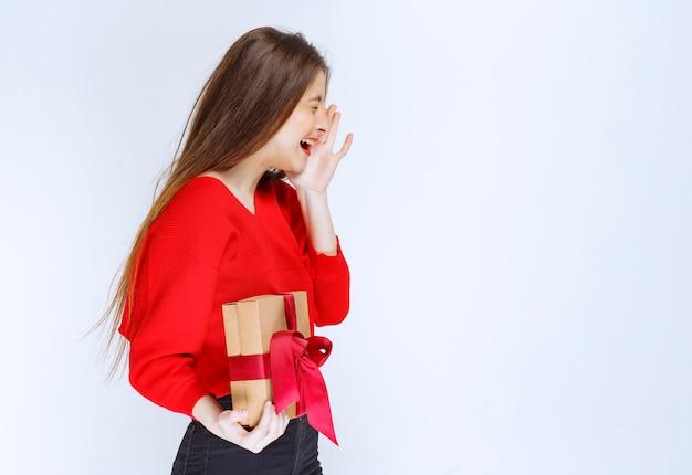 Dziewczyna trzyma czerwoną wstążką owinięte kartonowe pudełko i płacze i czuje się smutna.