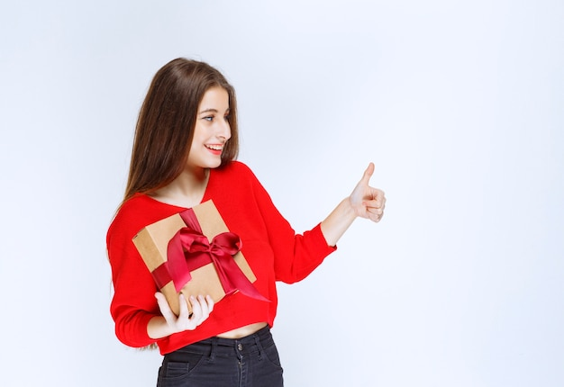 Dziewczyna trzyma czerwoną wstążką owinięte kartonowe pudełko i pokazując znak satysfakcji.