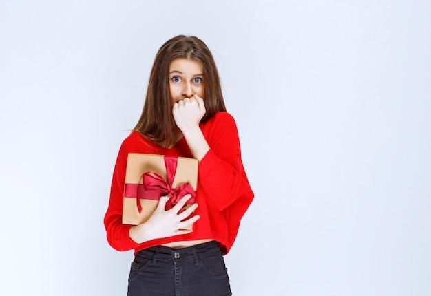 Dziewczyna trzyma czerwoną wstążką owinięte kartonowe pudełko i wygląda na zestresowaną i przerażoną.