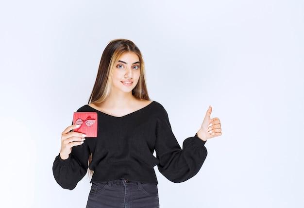 Dziewczyna trzyma czerwone pudełko i czuje się usatysfakcjonowana. zdjęcie wysokiej jakości
