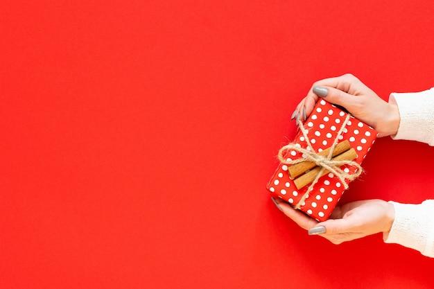 Dziewczyna trzyma czerwone pudełko w kropki z cynamonem na czerwonym tle, wesołych świąt i szczęśliwego nowego roku koncepcja, płaski świecki, widok z góry