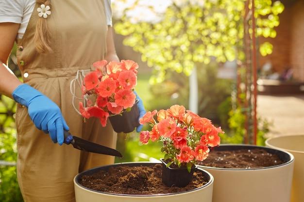 Dziewczyna trzyma doniczkę z kwiatami i małą łopatę.