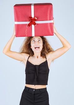 Dziewczyna trzyma duże czerwone pudełko nad głową.
