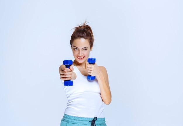 Dziewczyna trzyma dwa jednokilogramowe niebieskie hantle i trenuje z nimi.