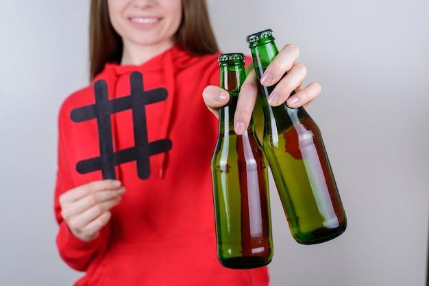 Dziewczyna trzyma dwie zielone butelki szklane i hashtag