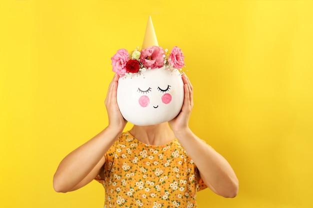 Dziewczyna trzyma dynię z halloweenowym makijażem na żółtym tle