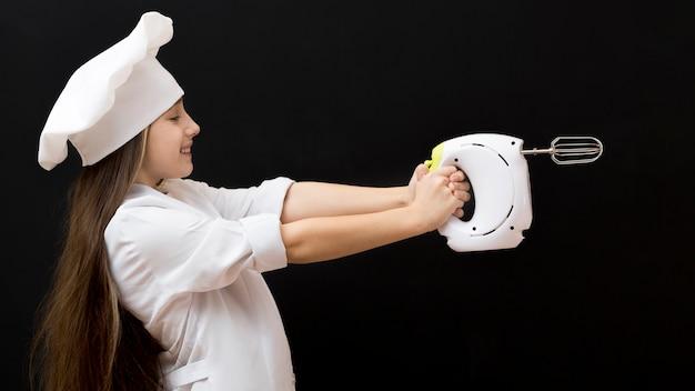 Dziewczyna trzyma elektrycznego melanżeru bocznego widok