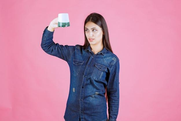 Dziewczyna trzyma filiżankę kawy do góry nogami