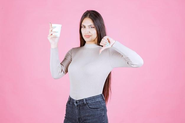 Dziewczyna trzyma filiżankę kawy i pokazuje kciuk w dół znak