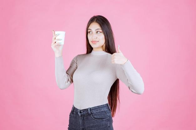 Dziewczyna trzyma filiżankę kawy i pokazuje kciuk znak