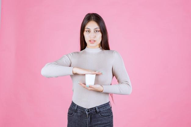 Dziewczyna trzyma filiżankę kawy w dłoniach