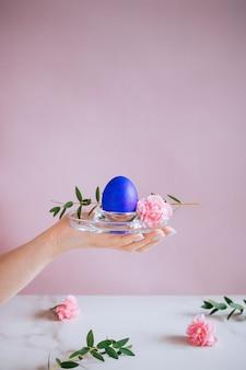 Dziewczyna trzyma fioletowe jajko na stojaku, różowe i marmurowe tło, minimalizm, kwiaty