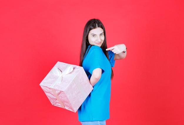 Dziewczyna trzyma fioletowe pudełko owinięte białą wstążką i chowa je za.