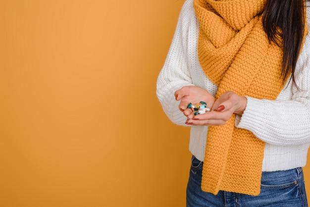Dziewczyna trzyma garść różnych wielobarwnych pigułek leków pigułki