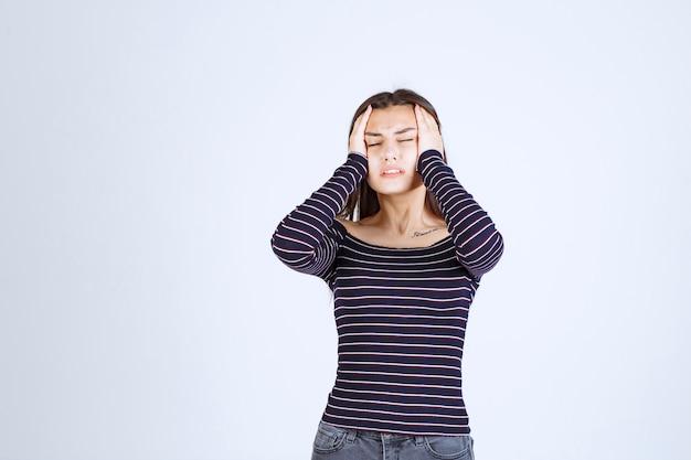 Dziewczyna trzyma głowę, gdy jest zmęczona lub ma ból głowy.