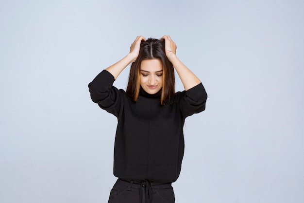 Dziewczyna trzyma głowę obiema rękami. zdjęcie wysokiej jakości