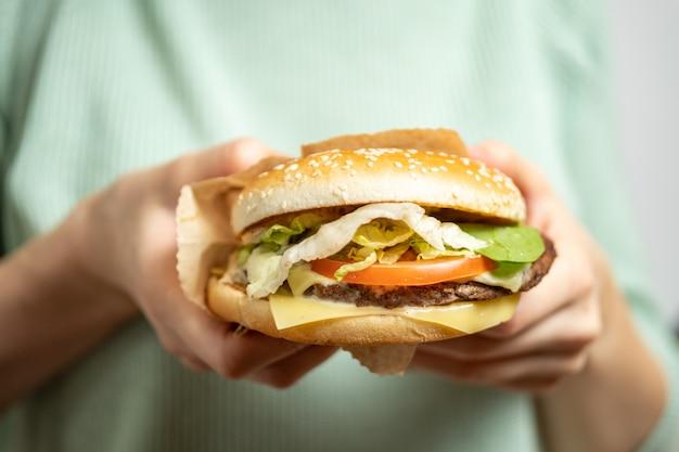 Dziewczyna trzyma hamburgera rękami.