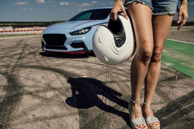 Dziewczyna trzyma hełm obok sportowego samochodu