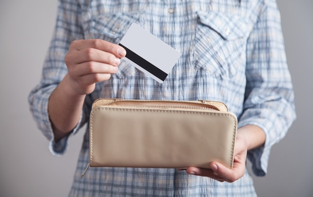 Dziewczyna trzyma i wkłada kartę kredytową do swojego portfela.