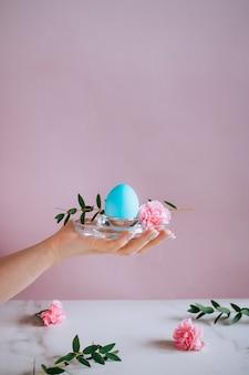 Dziewczyna trzyma jajko na niebieskim stoisku, różowe i marmurowe tło, minimalizm, kwiaty