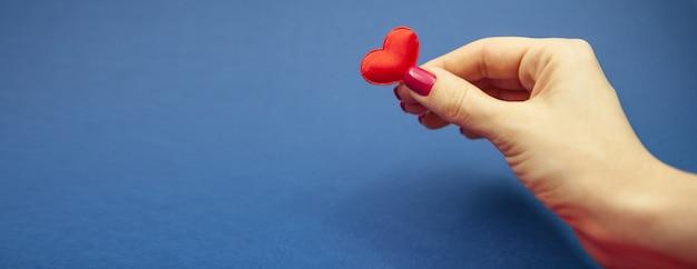 Dziewczyna trzyma jedno serce na niebieskim tle.