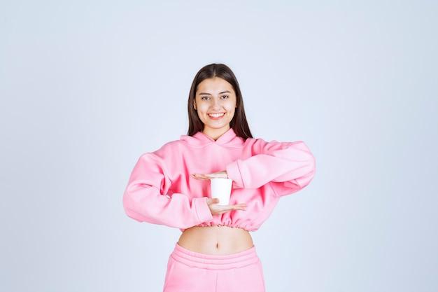 Dziewczyna trzyma jednorazową filiżankę kawy obiema rękami