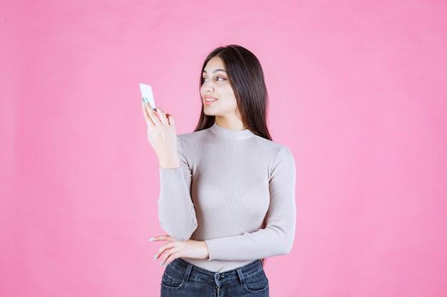 Dziewczyna trzyma jej nową wizytówkę i pozytywne samopoczucie