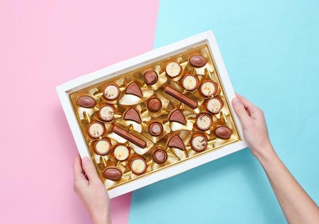 Dziewczyna trzyma jej ręce pudełko czekoladek w złotej tacy na pastelowym tle. widok z góry