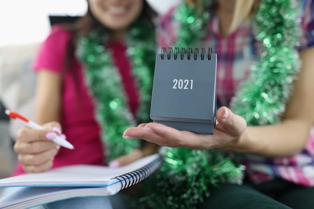 Dziewczyna trzyma kalendarz 2021 w dłoni.