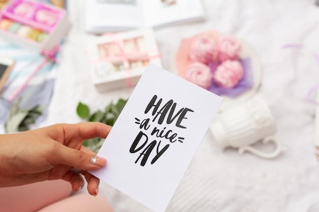 Dziewczyna trzyma kartę z napisem życzę miłego dnia