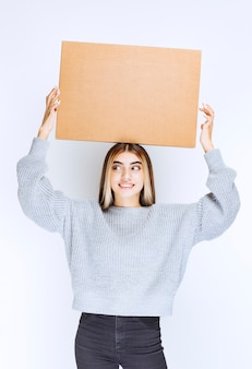 Dziewczyna trzyma kartonową paczkę nad głową.