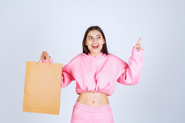 Dziewczyna trzyma kartonową torbę na zakupy i wskazuje powyżej.