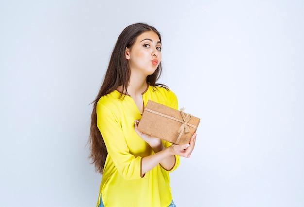 Dziewczyna trzyma kartonowe pudełko i czuje się pozytywnie.