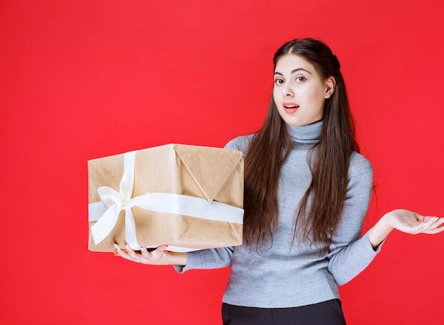 Dziewczyna trzyma kartonowe pudełko i wskazując na niego.