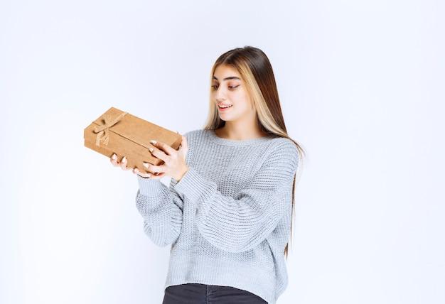 Dziewczyna trzyma kartonowe pudełko i wygląda na zdziwioną.