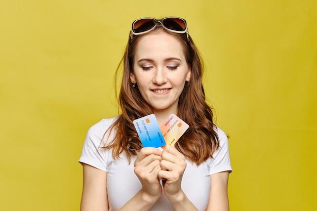 Dziewczyna trzyma karty kredytowe na żółtym tle.