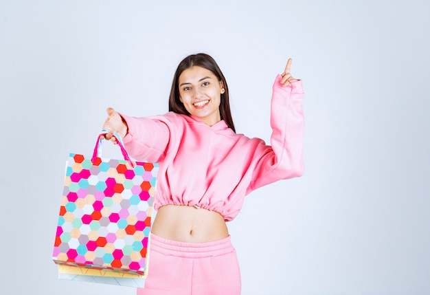 Dziewczyna trzyma kolorowe torby na zakupy i wskazuje gdzieś w górę.
