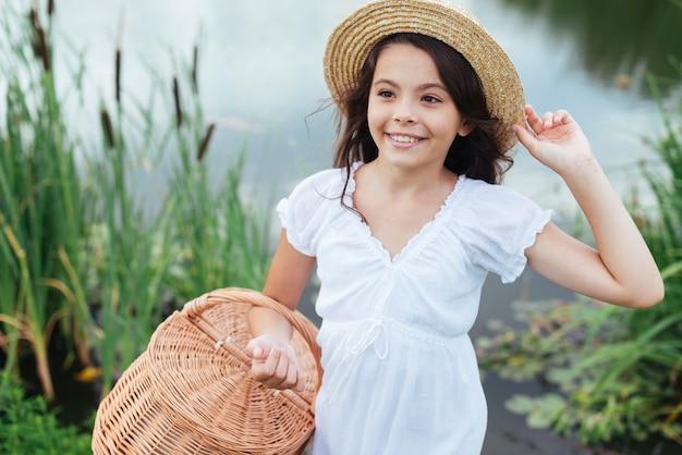 Dziewczyna trzyma kosz piknikowy nad jeziorem