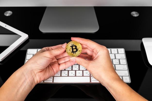 Dziewczyna trzyma kryptę w ręku na tle laptopa