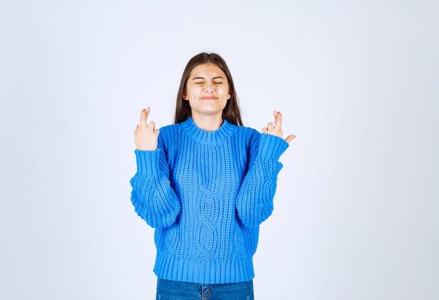 Dziewczyna trzyma krzyż palce na biało szary.