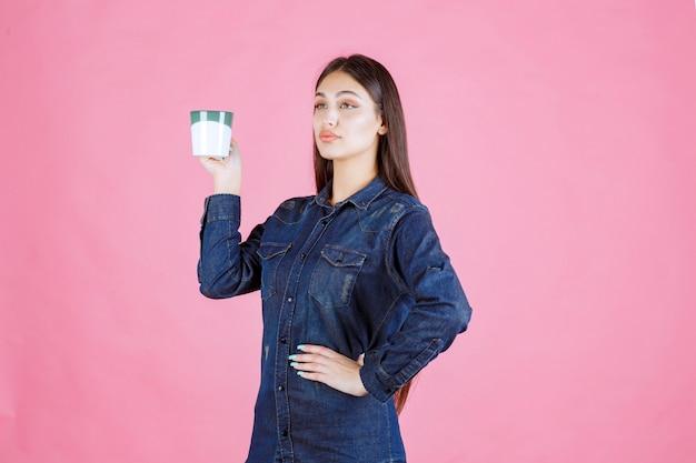 Dziewczyna trzyma kubek białej zielonej kawy i pachnie