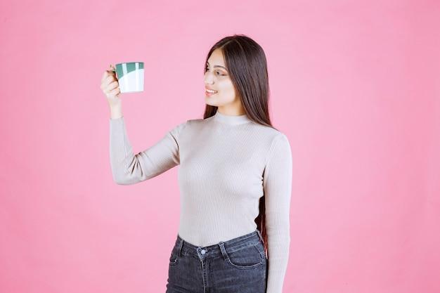 Dziewczyna trzyma kubek kawy biały kolor zielony i pozytywne samopoczucie
