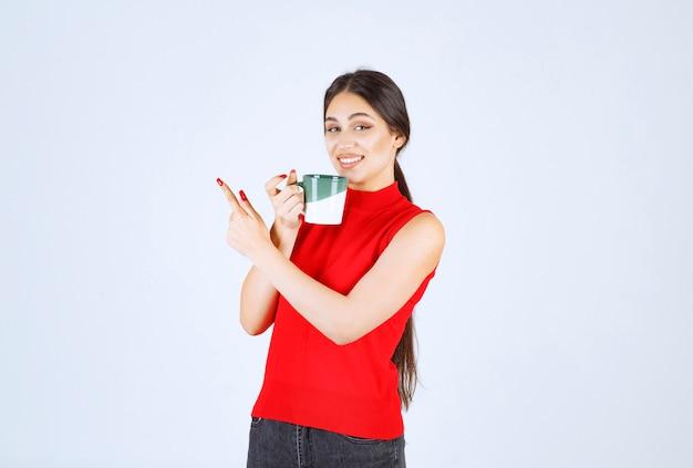 Dziewczyna trzyma kubek kawy i wskazuje na lewo.