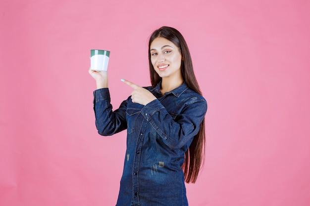 Dziewczyna trzyma kubek kawy i wskazuje na to