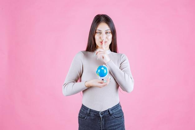 Dziewczyna trzyma kulę ziemską i robi znak ciszy
