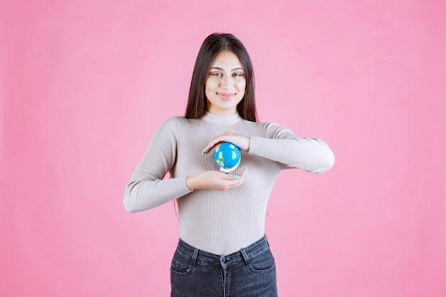 Dziewczyna trzyma kulę ziemską między rękami