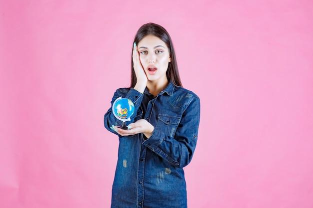 Dziewczyna trzyma kulę ziemską w dżinsowej kurtce i wygląda na zaskoczonego