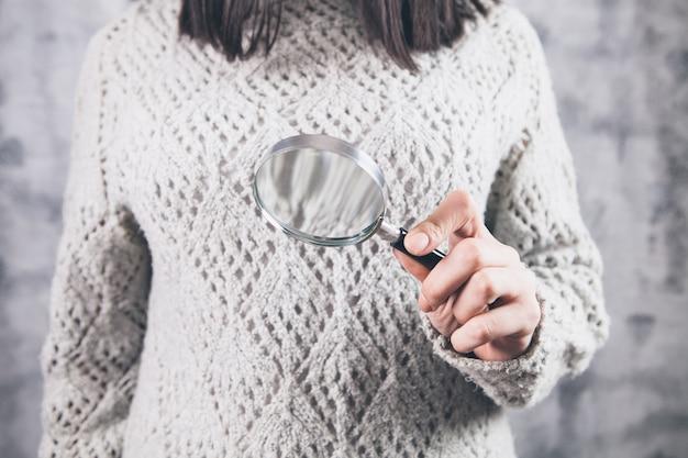 Dziewczyna trzyma lupę w dłoniach, szukać informacji