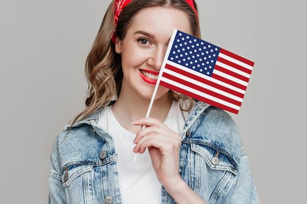 Dziewczyna trzyma małą amerykańską flagę i uśmiecha się na białym tle na pomarańczowym tle 4 lipca dzień niepodległości